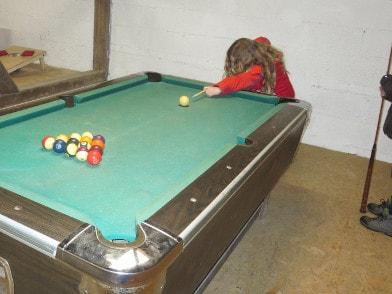 Kind beim Spielen von Billard in der Spielscheune