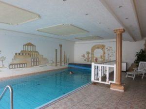 Frau beim Schwimmen im mediteranen Hallenbad