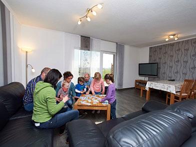 Familie beim Brettspiel im Wohnzimmer der Wohnungen Hedwig und Hubert