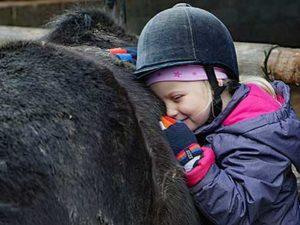 Kind beim Kuscheln mit einem Pony
