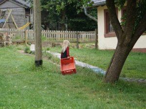Kind mit Kiste bei der Außenrollbahn
