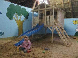 Mädchen beim Schaufeln im Sandkasten Indoor