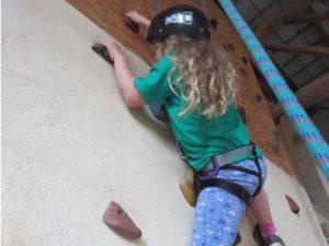Kind beim Klettern an der Kletterwand in der Spielscheune