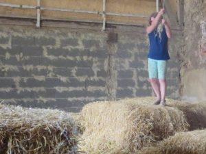 Mädchen beim Hangeln in der Strohscheune