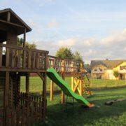 Spielplatz mit Hängebrücke und großer Rutsche im Park