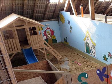 Sandkasten mit Sandpielzeug und Spielhaus in der Indoorhalle