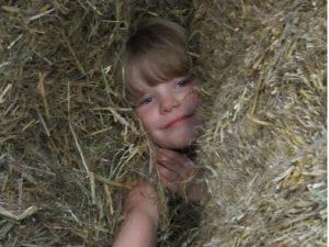 Kind in der Strohscheune versteckt im Stroh