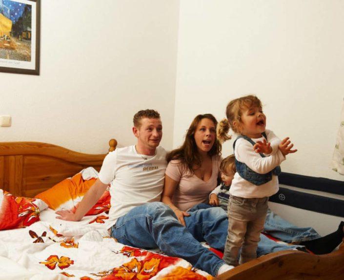 Eltern mit Kind im Schlafzimmer der Ferienwohnung