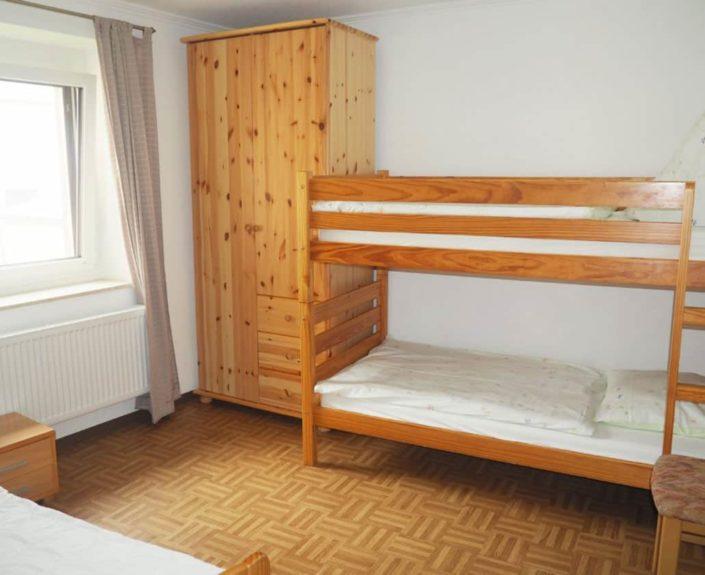 Kinderzimmer mit Einzelbett und Etagenbett in der Wohnung Valentin 1