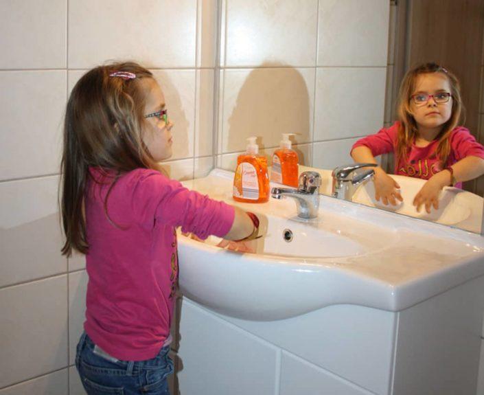 Kind beim Hände waschen im Waschbecken der Ferienwohnung Valentin 1