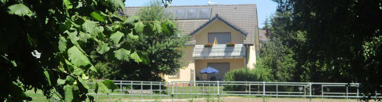 Bauernhofurlaub Eifel: Blick vom Reitplatz auf Ferienhaus