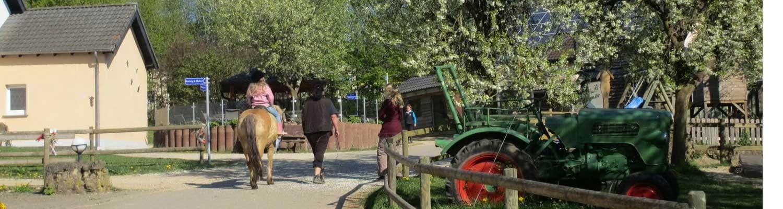 Gelände des Ferienhofes mit Reitern im Frühling