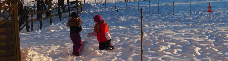 Kinder beim Schneemann bauen